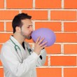 Male Doctor Blowing Air In Balloon — Stock Photo #24114627