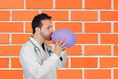 Male Doctor Blowing Air In Balloon — Stock Photo