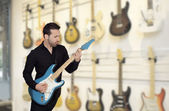 Attractive men playing a electric guitar — Stock Photo