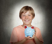 Smiling boy holding a blue piggy-bank — Stock Photo