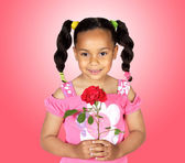 Smiling little girl with a red rose — Stock Photo