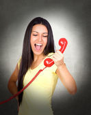 Attractive girl shouting at phone — Stock Photo