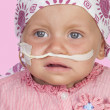 Adorable baby with a headscarf beating the disease - Stock Photo