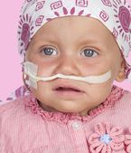 Adorable baby with a headscarf beating the disease — Stock Photo