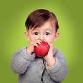 Adorable baby eating a red apple — Stock Photo