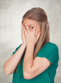 Beautiful shy girl with green t-shirt covering her face — Stock Photo