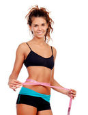 Slim brunette girl with tape measure and fitness clothes — Stok fotoğraf