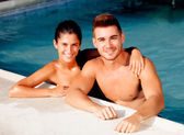 Happy couple relaxing in the pool — Stock Photo