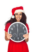 Girl in christmas hat with clock — Stock Photo