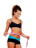 Slim brunette girl with tape measure and fitness clothes — Stock Photo