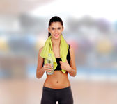 Woman in fitness with a towel drinking water — Foto de Stock