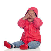 Adorable african baby sitting on the floor with red raincoat — Stock Photo