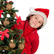 Stock Photo: Funny boy with santa hat behind Christmas tree claus