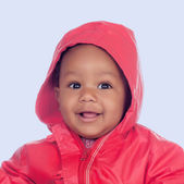 Adorable african baby with a beautiful smile and a red raincoat — Stock Photo