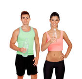 Young couple at the gym drinking water — Stock Photo
