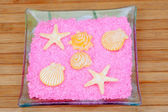 Soaps with shapes of shells and starfish on pink bath salts in a — Stock Photo