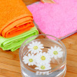 Two colorful towels next to a bowl of water with flowers — Stock Photo