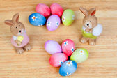 Funny rabbits ceramic with Easter eggs decorated with daisies — Stock Photo