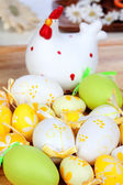 Yellow and green easter eggs with a ceramic hen — Stock Photo