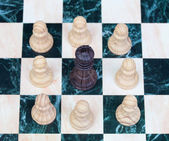The black king surrounded by white pawns — Stok fotoğraf