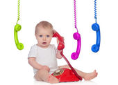Beautiful baby with many telephones — Stock Photo