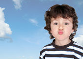 Funny child making grimace throwing a kiss — Stock Photo