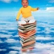 African baby sitting on stack of books — Stock Photo #46653587