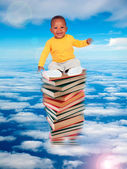 African baby sitting on stack of books  — ストック写真