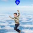 Child flying with a balloon — Stock Photo #47372829