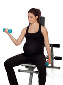 Pregnant woman lifting weights in the gym — Stock Photo