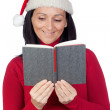 Beautiful girl with Christmas hat reading a book — Stock Photo #9507453