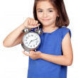 Brunette little girl with a silvered alarm-clock — Stock Photo #9630003