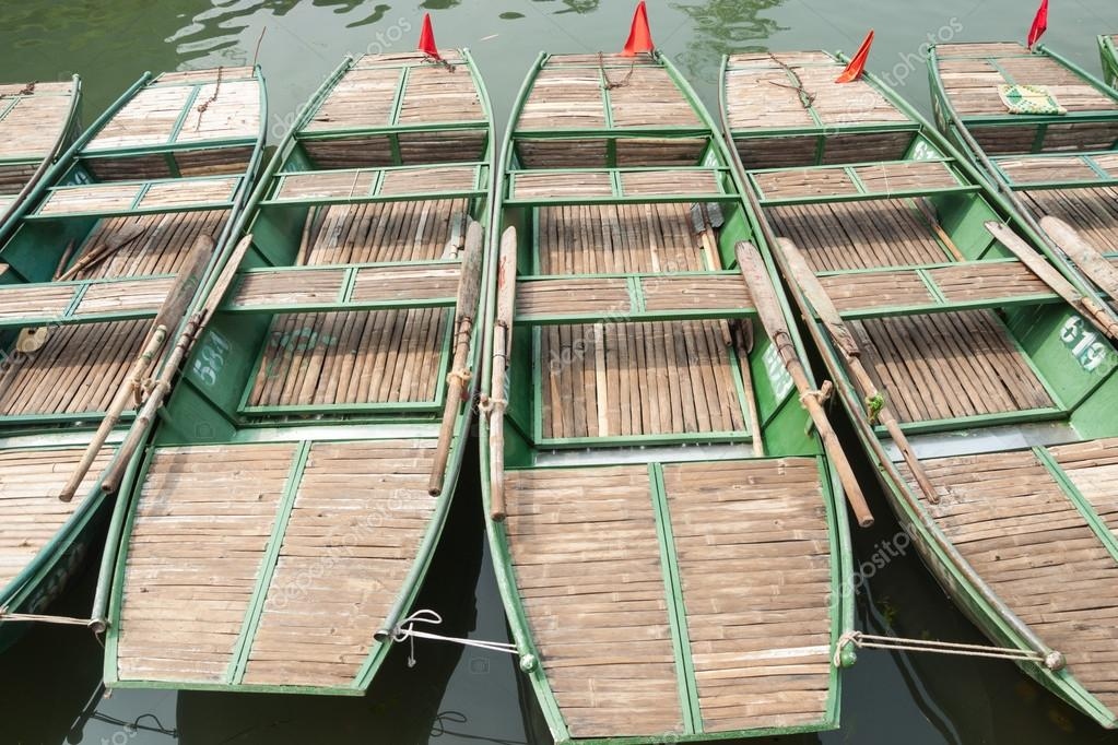 Many boats tied together on a river in Ninh Binh province, Vietnam. They are used to carry tourists to beautiful grottoes and caves to enjoy nature around. — Stock Photo #13775334