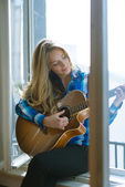 Young woman playing guitar on window — Stock Photo