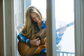 Young woman playing guitar on window — Stok fotoğraf