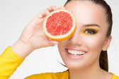 Young brunette with red grapefruit in her hand — Stock Photo