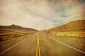 Grunge image of highway and blue sky — Stock Photo