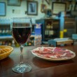 Glass of wine and jamon plate — Stock Photo