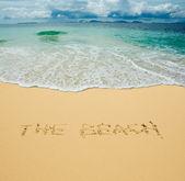 The beach written in a sandy tropical beach — Stock Photo