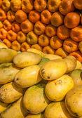 Yellow mangos and tangerines at fruit market — Stock Photo
