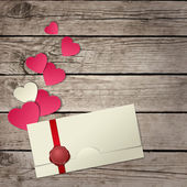 Paper hearts and envelope on wooden background — Stock Photo