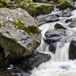 Fresh water flowing along a steep and rocky section of river - Stock Photo