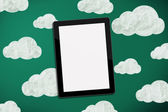 Tablet on chalk board with clouds — Stock Photo