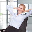 Happy young businesswoman relaxing on chair — Stock Photo