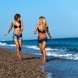 Attractive girl friends running along seaside. — Stock Photo #12792325