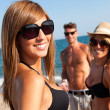 Attractive girl with friends on beach. — Stock Photo