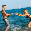 Attractive girl splashing her boyfriend on beach. — Stock Photo