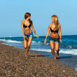 Attractive two young girl friends running at seaside. — Stock Photo