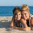 Close up portrait of two girl friends on beach. - Stock Photo
