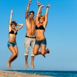 Stock Photo: Group of young friends jumping on beach.